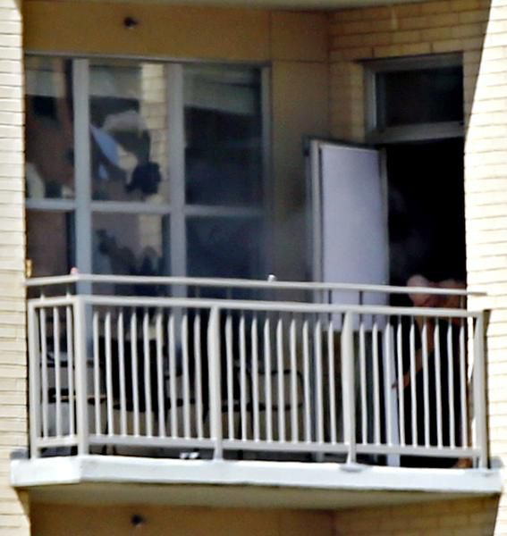 The suspect opened a patio door for fresh air after police lobbed gas canisters into the apartment.