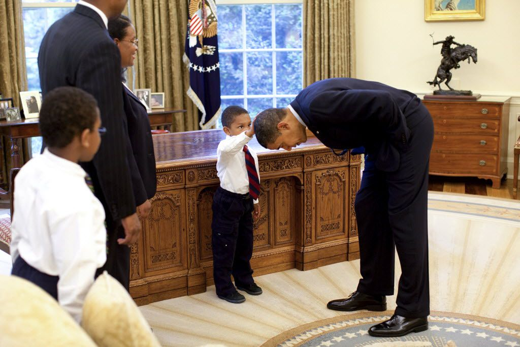 An undated handout photo of Jacob Philadelphia, 5, center, the son of a White House staff member, touches President Barack Obama's hair to see if it feels like his, in the Oval Office of the White House in Washington.