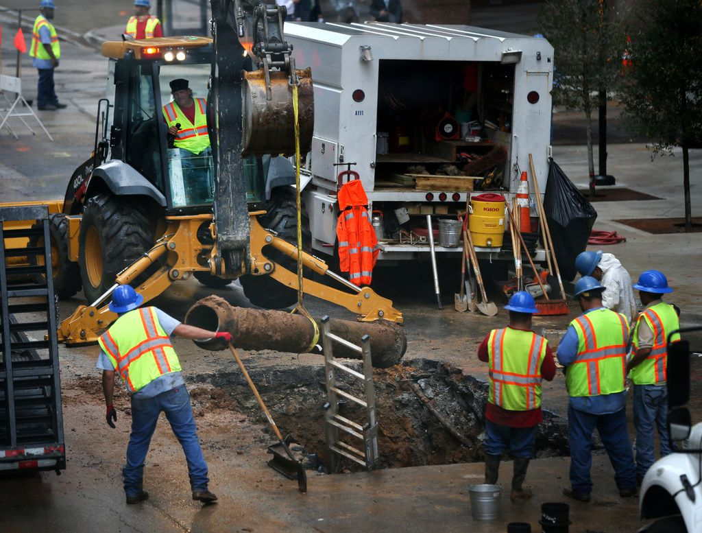 Crews remove a broken water main at St. Paul and Elm streets in downtown Dallas on Friday, Aug. 10. The broken waterline sent water gushing through downtown Dallas, closed roads and shut down water service in the area.
