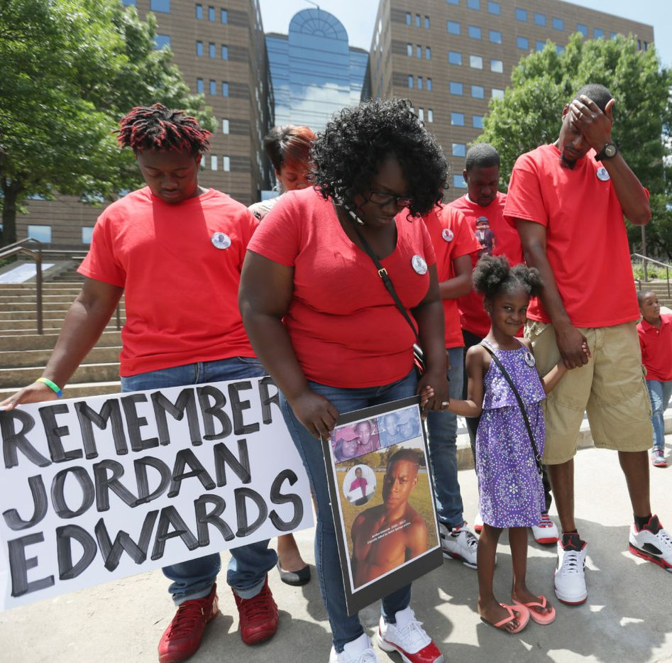 On May 13, Jordan Edwards' stepmother, Charmaine Edwards, held a photo of her slain son as she stood with son Vidal Allen (left) and husband Odell Edwards and other family members during a prayer outside the courthouse in Dallas.