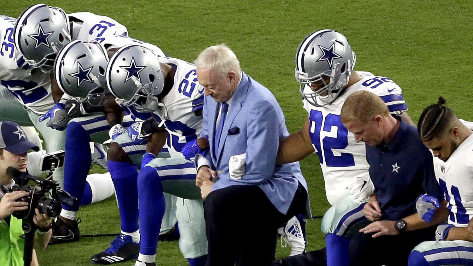 Jugadores de los Cowboys de Dallas y su dueño Jerry Jones se hincan antes de la interpretación del himno nacional el lunes por la noche antes del partido ante los Cardinals de Arizona.(AP)