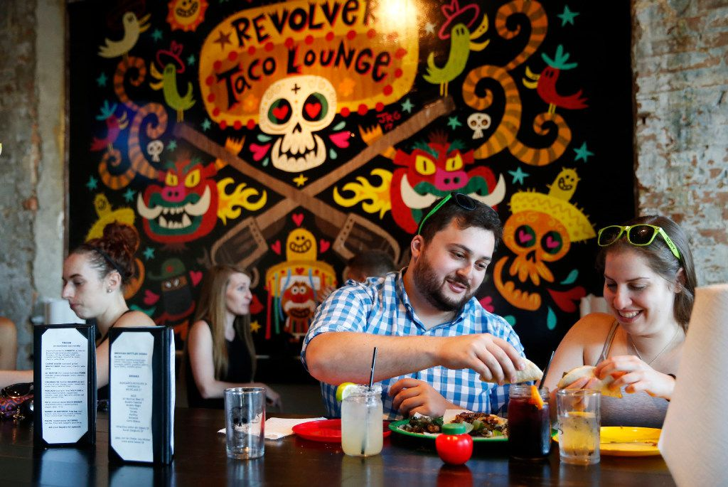 Diners at Revolver Taco Lounge's communal table (Vernon Bryant/The Dallas Morning News)