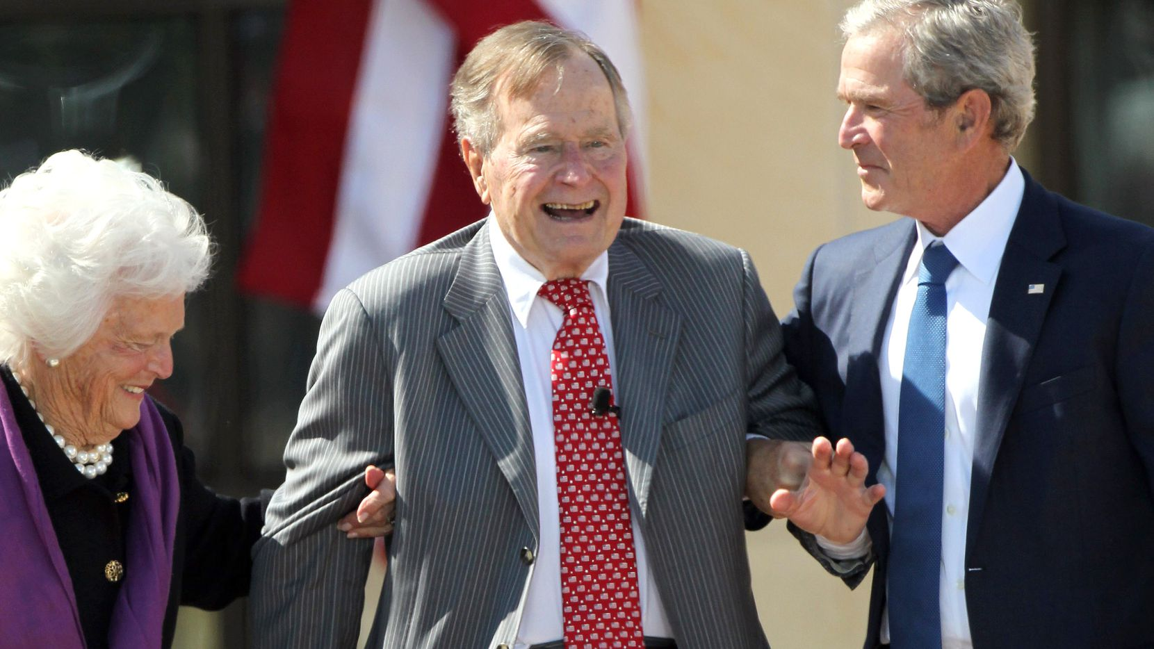 Former First Lady Barbara Bush and former President George W. Bush help former President George H.W. Bush to his feet as they acknowledge applause at the dedication of the George W. Bush Presidential Center in Dallas on April 25, 2013.