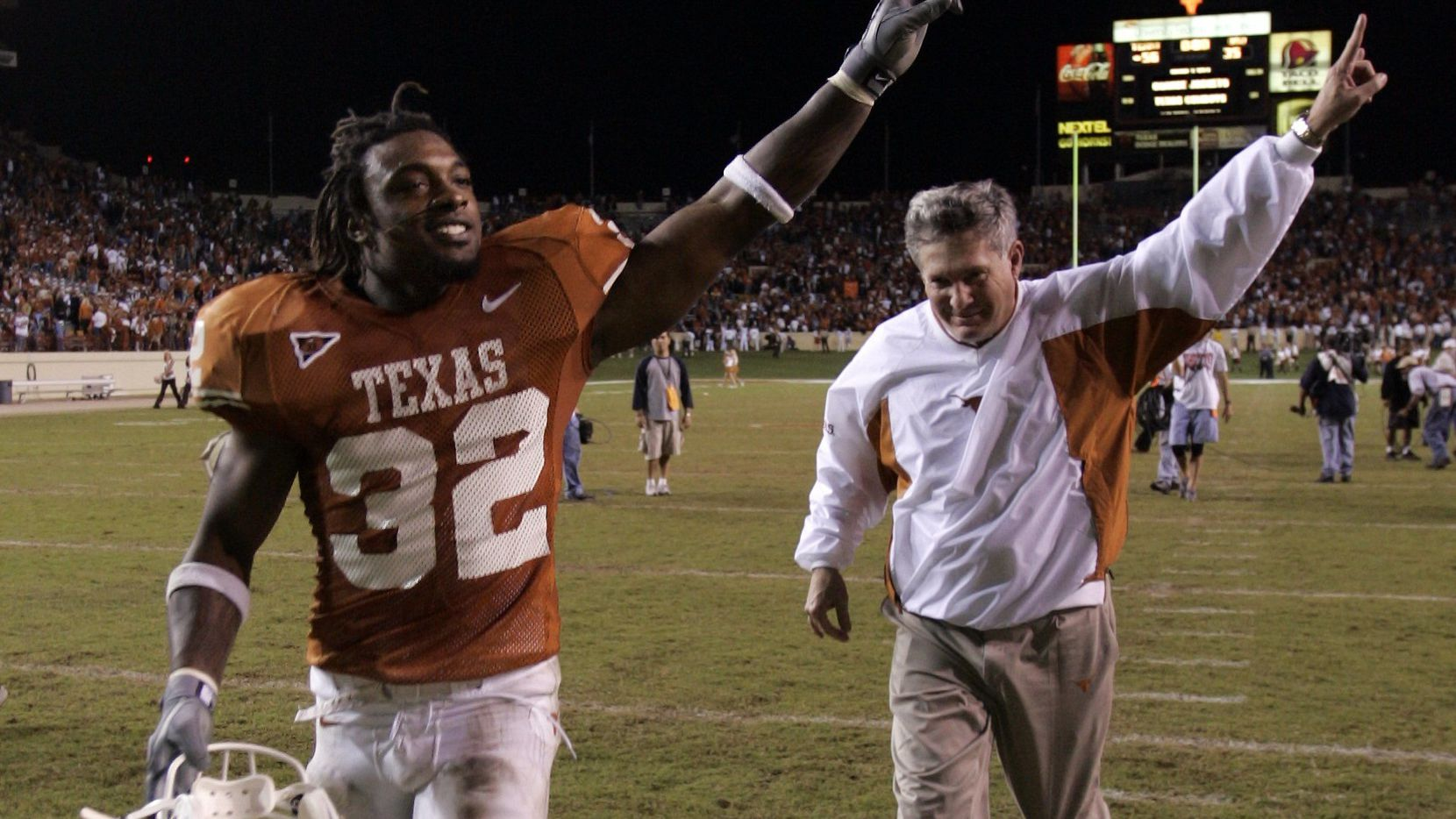 11/6/04 - Austin, Texas -  Texas running back Cedric Benson (32) and head coach Mack Brown salute Longhorn fans after the biggest comeback in Texas history, beating Oklahoma State University 56-35 at Royal-Memorial Stadium.