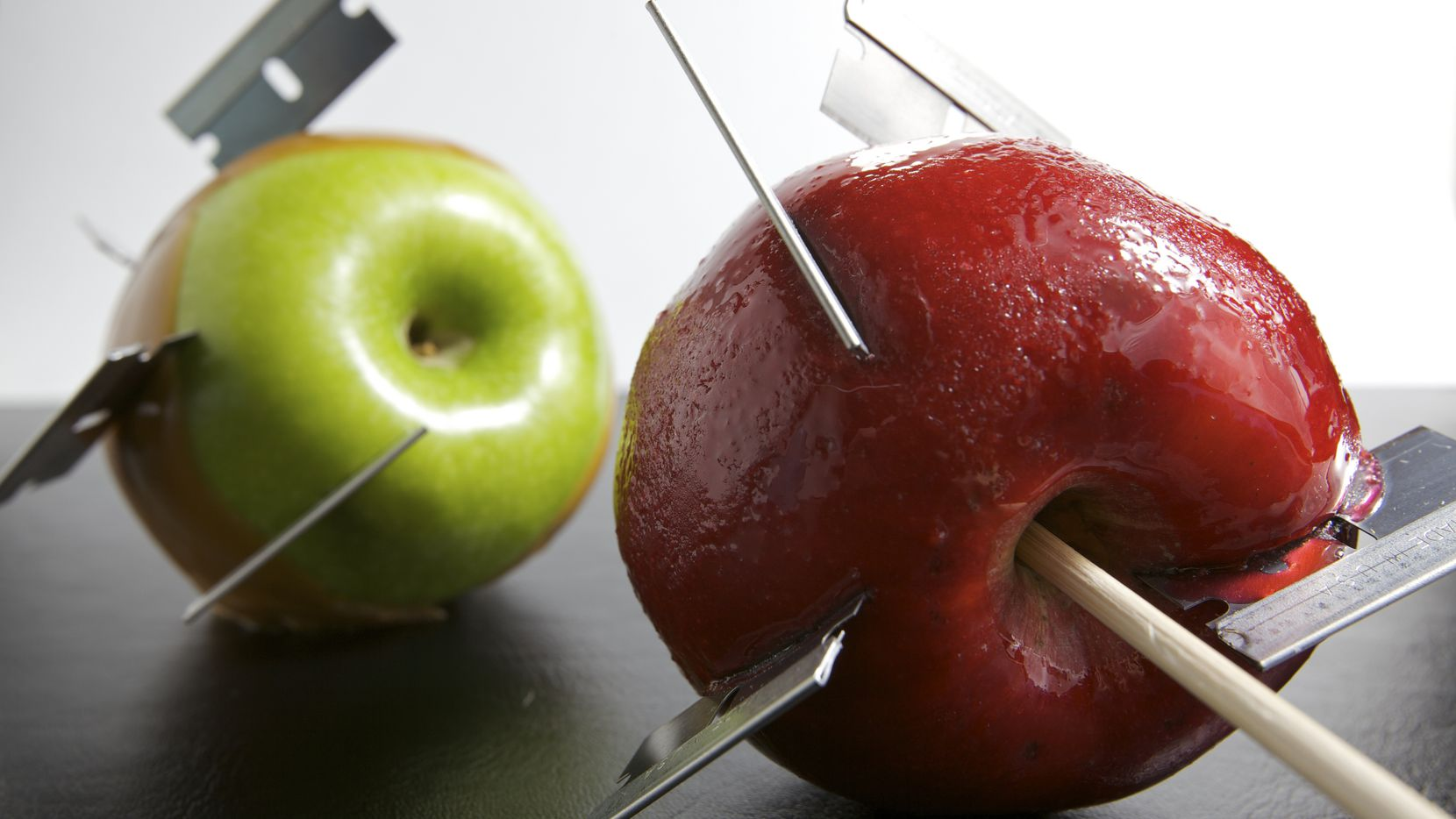 One green caramel apple, and one red candy apple with razor blades.