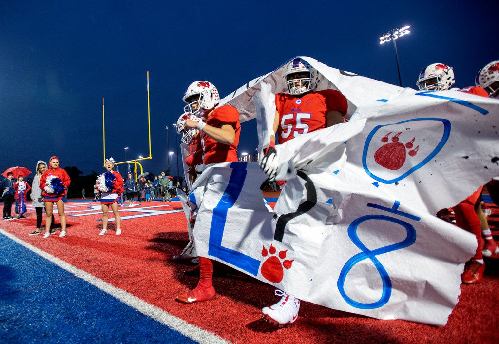 Parish Episcopal sophomore quarterback Preston Stone (2), left, and senior lineman Sam Burns (55) walk through a banner before a high school football game against Bishop Lynch on Friday, October 19, 2018 at Gloria H. Snyder in Dallas.  Parish won 27-20. (Jeffrey McWhorter/Special Contributor)