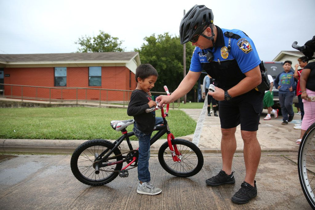 McKinney neighborhood police officer Randy Patton gives a sticker to Damian Valencia, 5, while patrolling the east neighborhood of downtown McKinney. (Rose Baca/The Dallas Morning News)