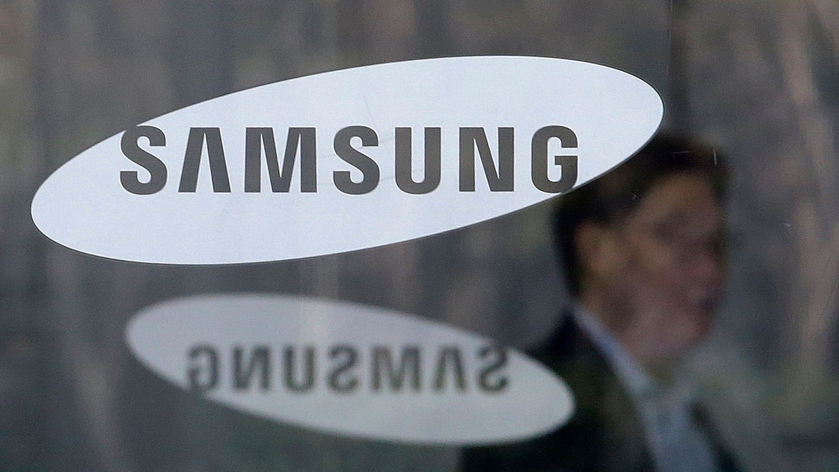 FILE - In this April 6, 2018 file photo, An employee walks past logos of the Samsung Electronics Co. at its office in Seoul, South Korea. Samsung Electronics said Thursday, April 26, 2018 its first-quarter earnings jumped 52 percent over a year earlier thanks to its mainstay memory chips that posted another record-high quarterly profit. (AP Photo/Ahn Young-joon, File)