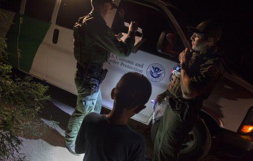 Unos agentes de la Patrulla Fronteriza, Edgar Cano (der.), y Richard Schweitzer (izq), procesan a un menor no acompañado, Darwin, de 11 años de edad, que cruzó sin documentos el Río Grande, en Hidalgo, Texas.  Foto AP