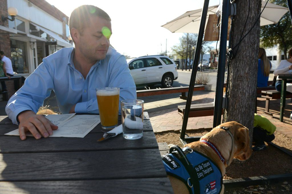 Dustin Deweerd stops to grab a drink at Oddfellows with his 3-year-old Labrador service dog Gunny on March 20, 2014 in Dallas. Gunny helps Deweerd, a U.S. Army veteran, cope with his Post Traumatic Stress Syndrome after serving in Irag and Afghanistan for two years. (Rose Baca/Neighborsgo Staff Photographer) 04072014xMETRO