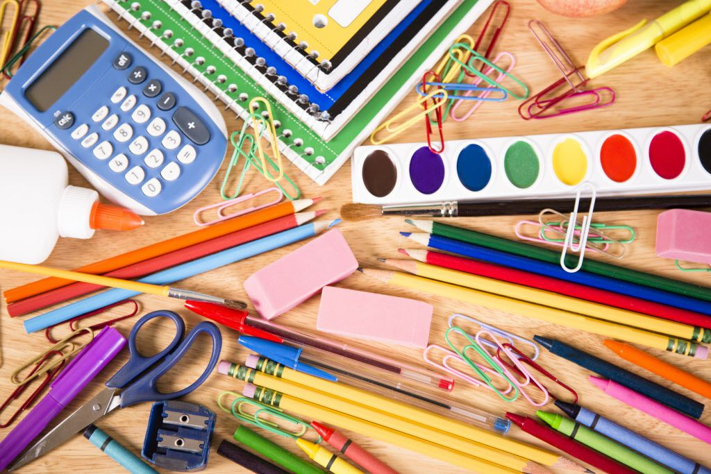 It's back to school time!  A large pile of elementary school supplies including: notebooks, calculator, watercolor paints, pencils, pens, erasers, glue, markers, crayons, and more.  The supplies are laying on a school desktop.  Education themed background.