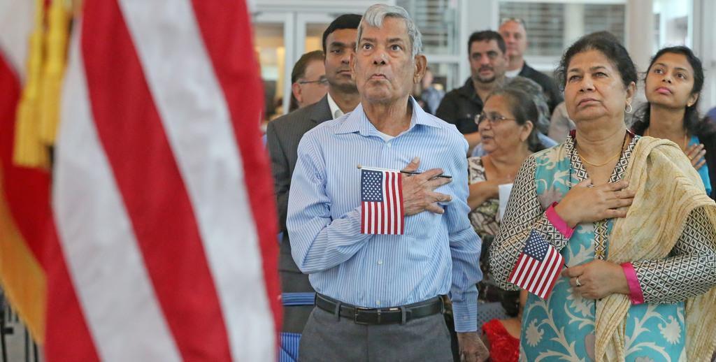 Mohammad Jameel y Shahnaz Parveen, de Pakistán, escuchan el himno durante su ceremonia de naturalización. LOUIS DeLUCA/DMN