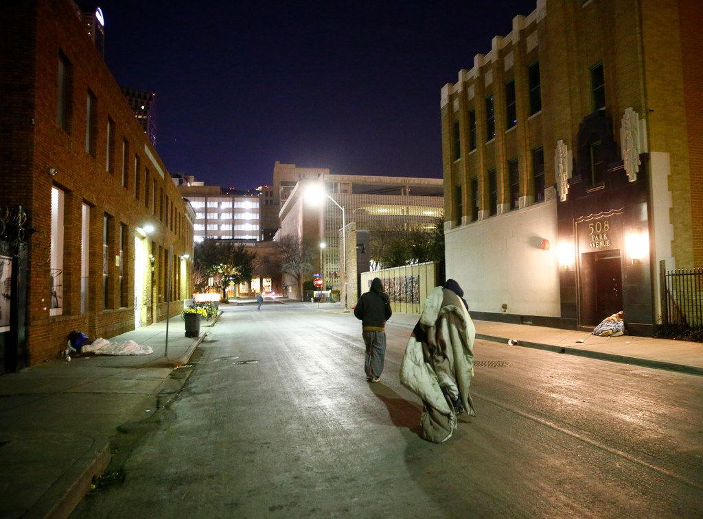 People move their blankets down Park Avenue next to The Stewpot in downtown Dallas on Jan. 16, 2018.