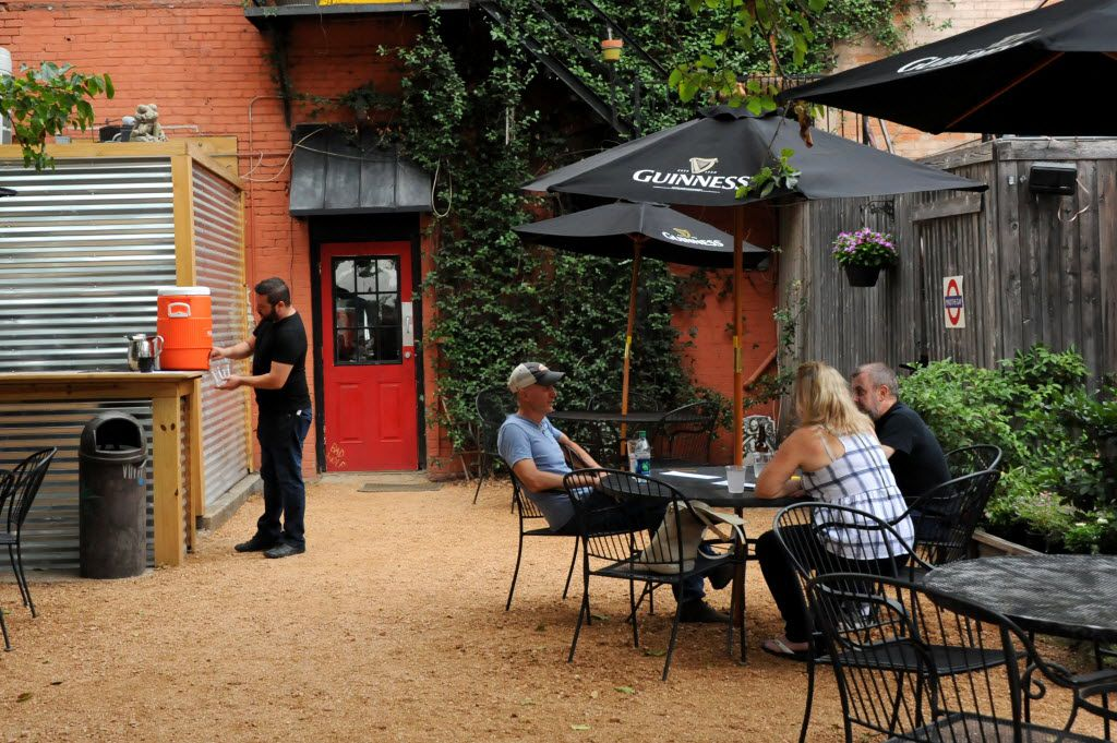 Patrons enjoy the back patio at Eight Bells Alehouse in Expo Park Dallas, TX on August 29, 2015.