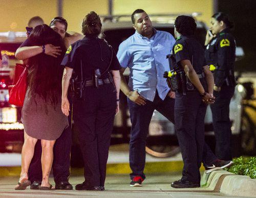 Una mujer recibe el abrazo de un oficial afera de la sala de emergencia del hospital Texas Health Presbyterian. El martes se confirmó la muerte del policía Rogelio Santander. ASHLEY LANDIS/DMN