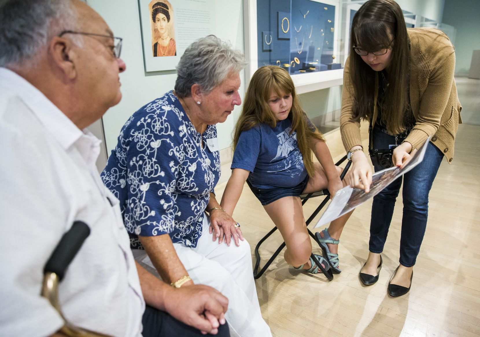 Alan and Hope Levine and their granddaughter Gretchen Jones, 9, looks at a photo of artwork from ancient Greece held by teaching specialist Jennifer Sheppard (right) as part of the Meaningful Moments Program for individuals with early stages of dementia at the Dallas Museum of Art.