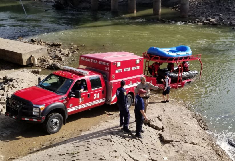Rescue workers scan the Trinity River during efforts to pull a car from the river on Tuesday.