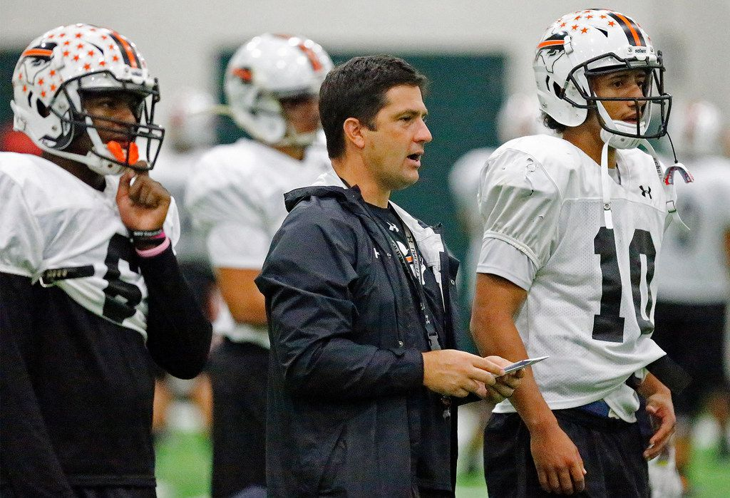 Haltom High School head coach Jason Tucker (center) stands between running back Kenneth Cormier (left) and quarterback Michael Black as Haltom High School held practice indoors at Southlake Carroll High School due to weather conditions on Wednesday, October 17, 2018.  (Stewart F. House/Special Contributor)