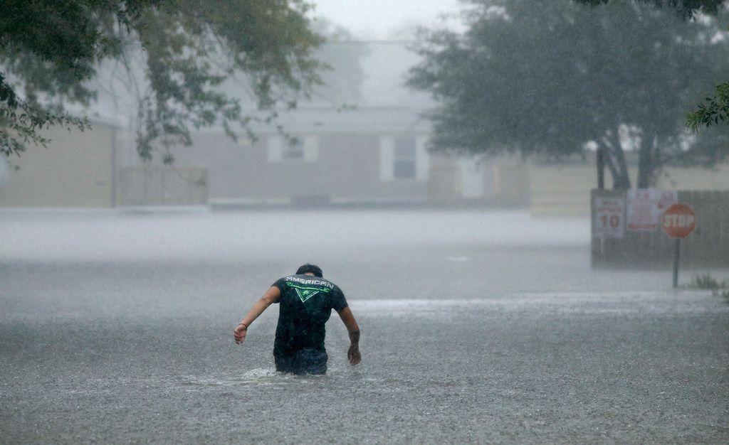 In a driving rainstorm, a man heads back into the flooded Pearland Acres mobile home community to help rescue and save residents' belongings in rural Pearland last August.