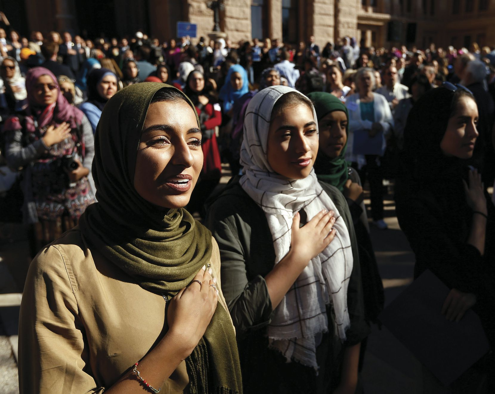 Hiba Loya and Donia Kased, both of Houston, join in the singing of the national anthem outside the Texas Capitol during the Texas Muslim Capitol Day rally in Austin in January.