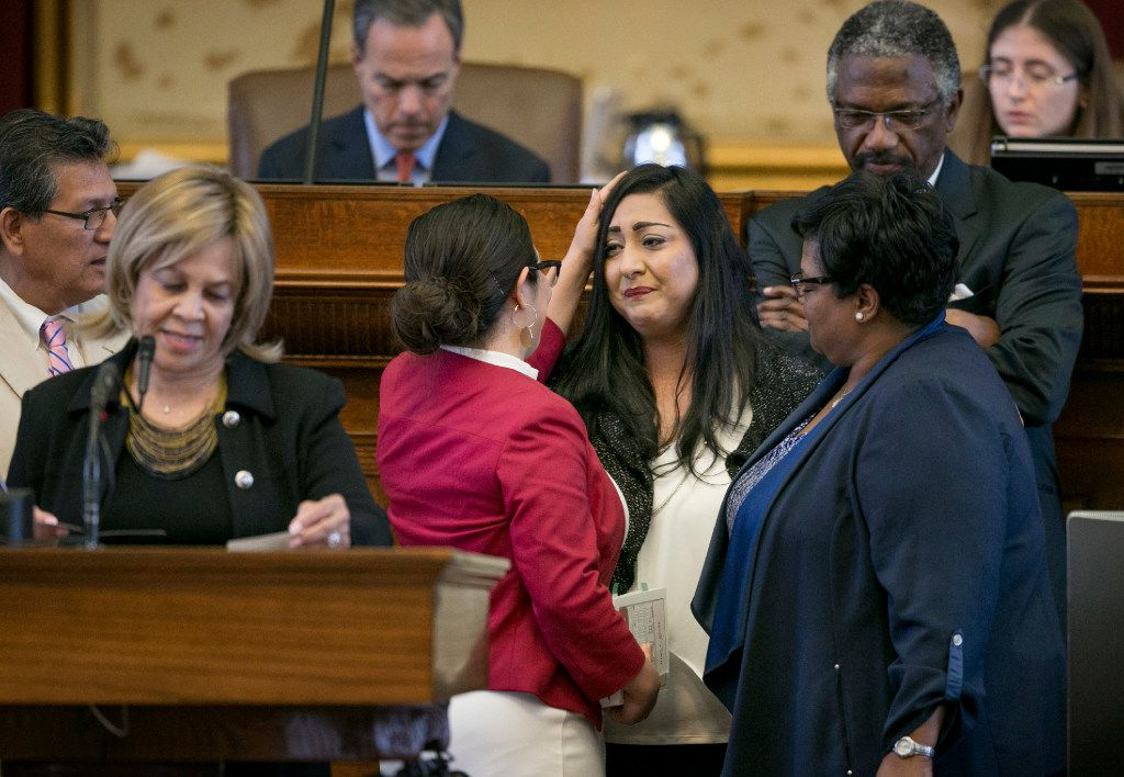 """State Rep. Mary Gonzalez, D-Socorro, left, back to camera, consoles state Rep. Diana Arevalo, D-San Antonio, shortly before the affirmative vote on SB 4, the sanctuary cities bill, at the Capitol in Austin, Texas, on Thursday April 27, 2017. The Texas House gave final approval Thursday to a bill banning """"sanctuary cities."""" (Jay Janner/Austin American-Statesman via AP)"""