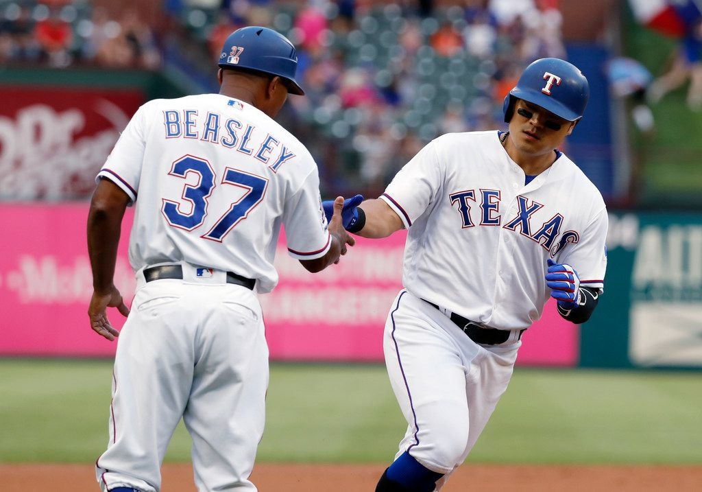 Texas Rangers third base coach Tony Beasley congratulates Shin-Soo Choo, right, who heads home after hitting a leadoff home run off Baltimore Orioles' Dylan Bundy during the first inning of a baseball game in Arlington, Texas, Tuesday, June 4, 2019. (AP Photo/Tony Gutierrez)