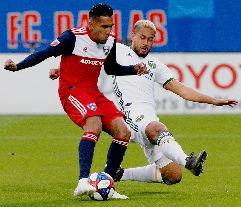 FC Dallas forward Jesus Ferreira, left, shoots for the first goal of the game as he is defended by Portland Timbers defender Bill Tuiloma (25) during the first half of an MLS soccer match in Frisco, Texas, Saturday, April 13, 2019. (Stewart F. House/The Dallas Morning News via AP)