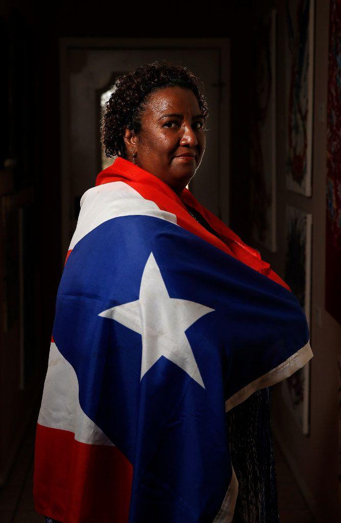 Sara Rosado, draped in a Puerto Rican flag, lives in Arlington.