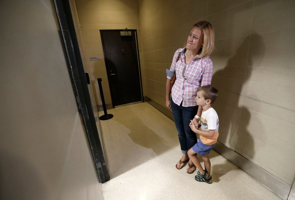 Luke Swofford (right), 4, and his mother Nikki Swofford wait outside the Lost and Found office.
