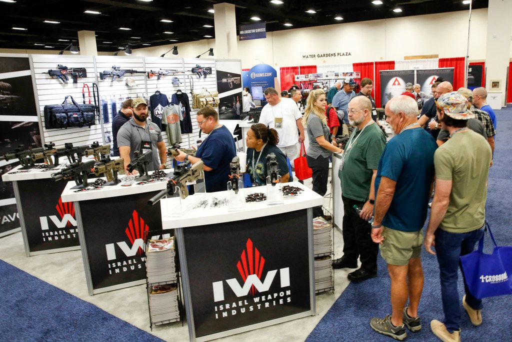 Patrons shop for guns and accessories in the Israel Weapon Industries booth at the Fort Worth Convention Center.