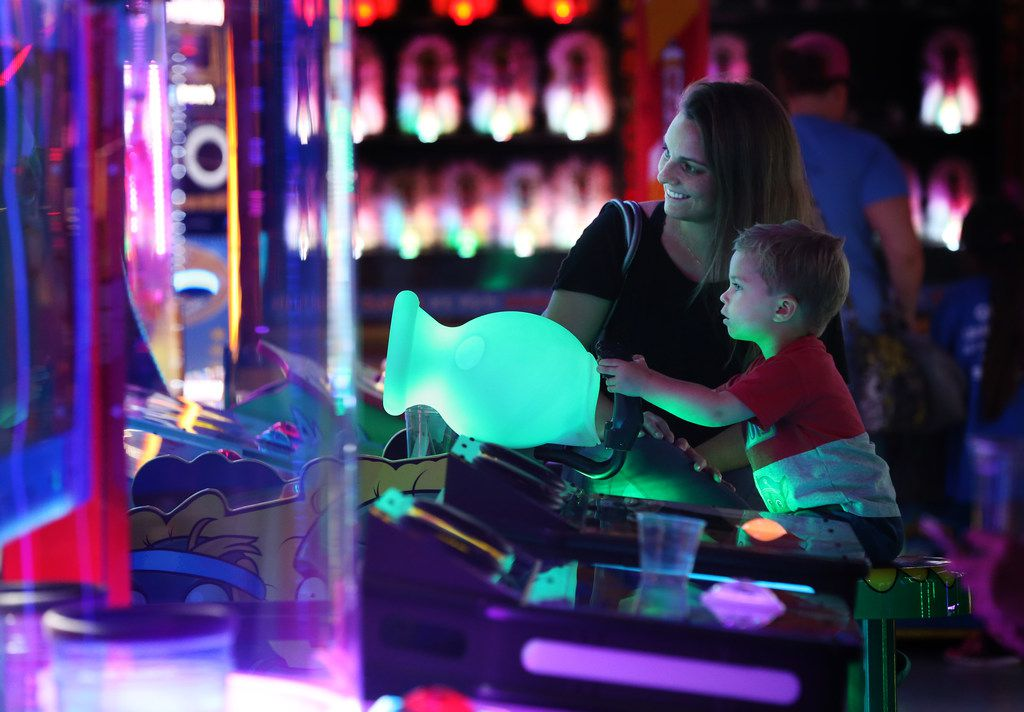 Lindsey Blackman watches her son Miles Blackman, 3, play an arcade game at NickelRama in Garland.