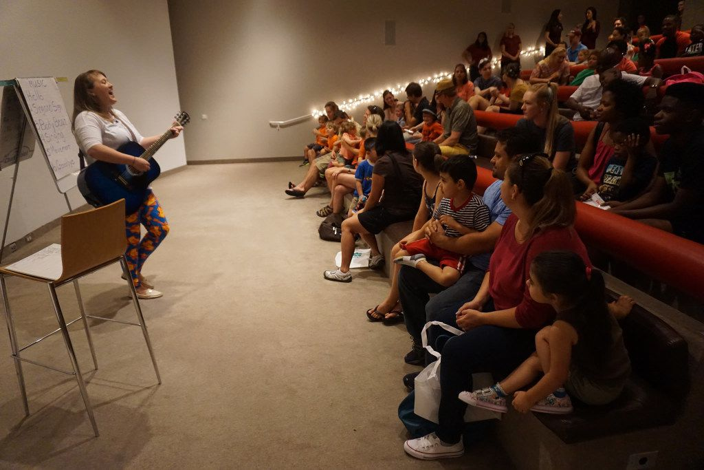 A music therapist leads families through songs about the Dallas Museum of Art's works at one of the Autism Awareness Family Celebrations.