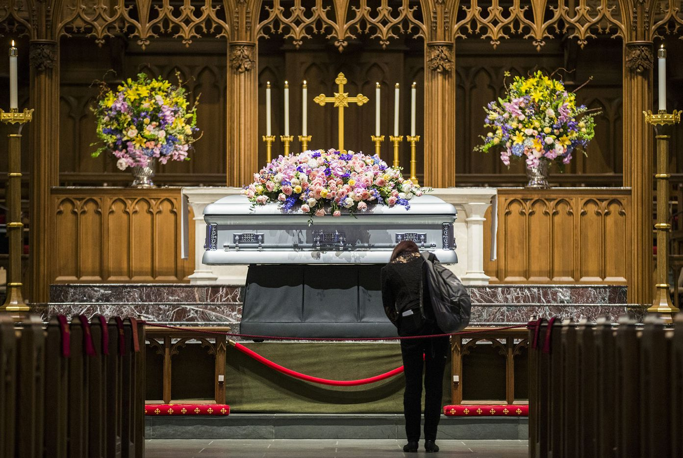 A woman bows in front of the casket of former first lady Barbara Bush on Friday, April 20, 2018 at St. Martin's Episcopal Church in Houston. Bush died on Tuesday and her funeral services are on Saturday. (Ashley Landis/The Dallas Morning News)
