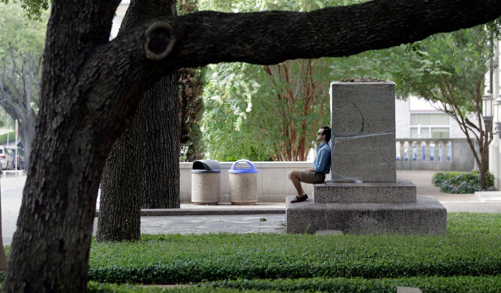 """A man who asked not to be identified sits at the base of a pedestal wrapped in plastic that had held a statue of Confederate Gen. Robert E. Lee, which was removed from the University of Texas campus early Monday morning, Aug. 21, 2017, in Austin, Texas. University of Texas President Greg Fenves ordered the immediate removal of statues of Robert E. Lee and other prominent Confederate figures from a main area of campus, saying such monuments have become """"symbols of modern white supremacy and neo-Nazism.""""(AP Photo/Eric Gay)"""