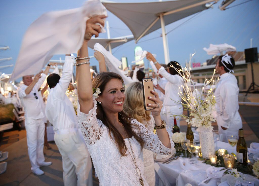 Laura West waves her napkin to signal dinner time during the inaugural Diner en Blanc Dallas on the Continental Avenue Bridge in Dallas on Sept. 17, 2015. Exactly 1,678 people attended the event, which requires dinner guests to dress all in white and bring their own tables, chairs and centerpieces. As per tradition, the location was kept private leading up to the event.