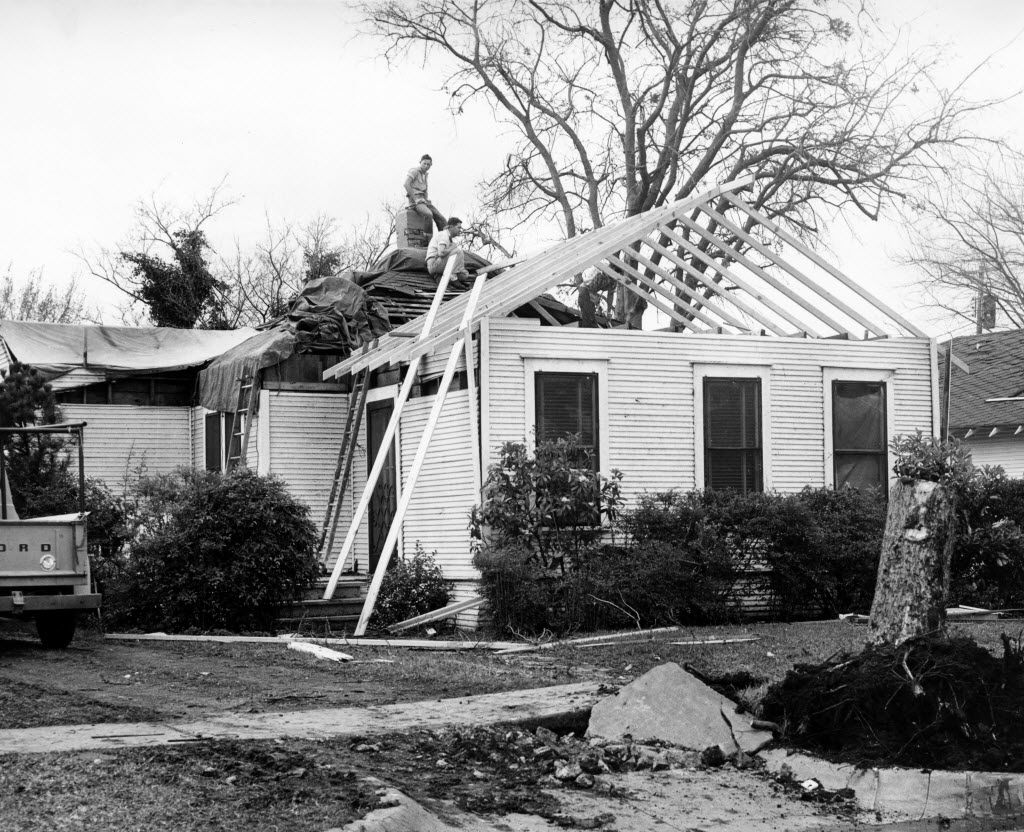 A work crew repairs a home damaged by the tornado that tore through Dallas in April 1957.