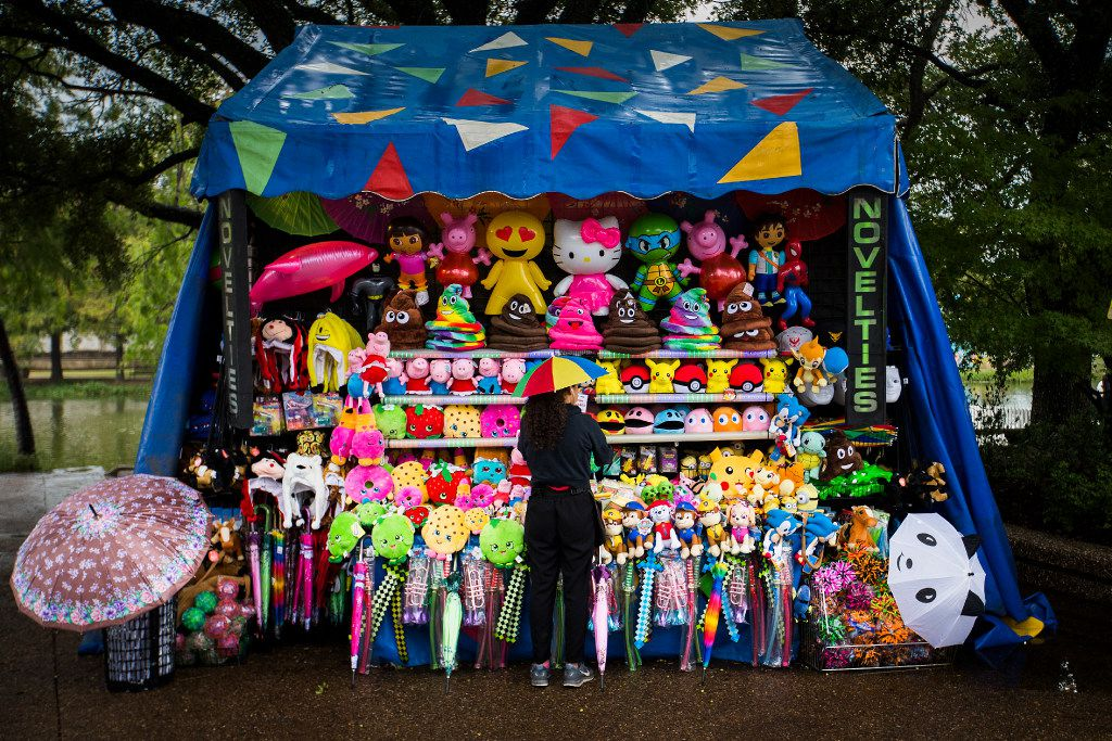 Renna Nasser wears a rainbow umbrella hat as she arranges novelty merchandise as a light rain falls during the State Fair of Texas at Fair Park on Friday, Oct. 14, 2016, in Dallas. (Smiley N. Pool/The Dallas Morning News)