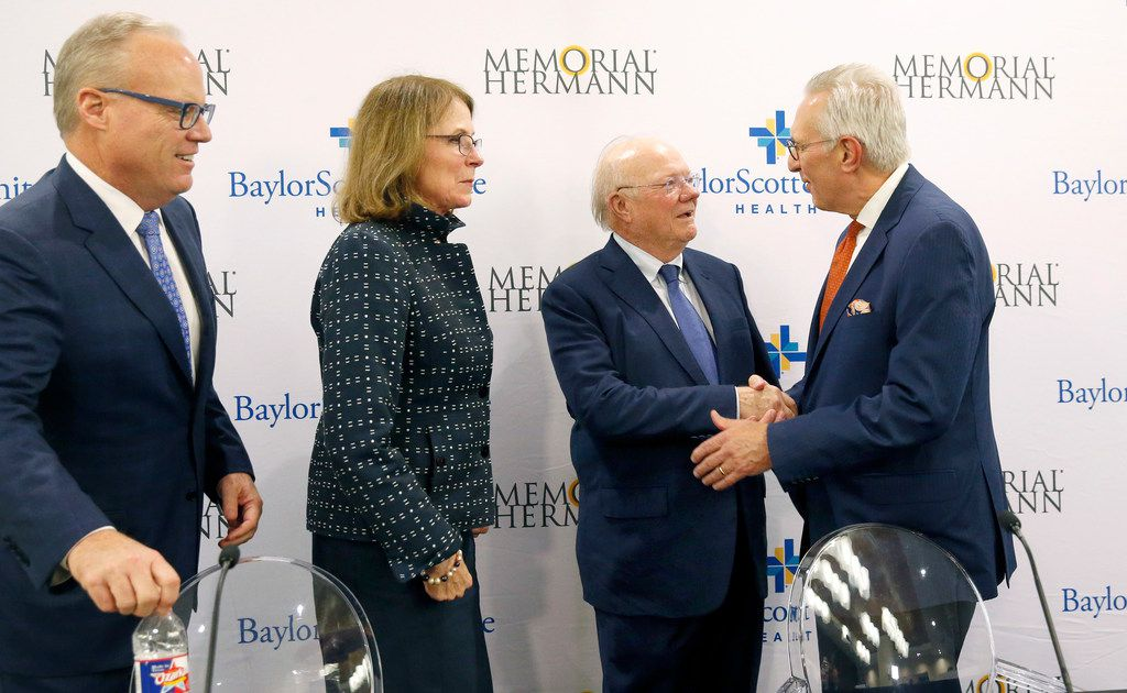 (from left) Jim Hinton, CEO of Baylor Scott and White Health; Deborah Cannon, Chair of Memorial Hermann Health System Board of Directors, Ross McKnight, Chair of Baylor Scott and White Holdings Board of Trustees and Chuck Stokes, president and CEO of Memorial Hermann Health System shake hands and visit following a news conference at Baylor Charles A. Sammons Cancer Center in Dallas. The press conference was to announce the intended merger of Baylor Scott and White with Memorial Hermann Health System, October 1, 2018. The boards of both non-profit hospitals have signed a letter of intent to merge into a combined system. (Tom Fox/The Dallas Morning News)