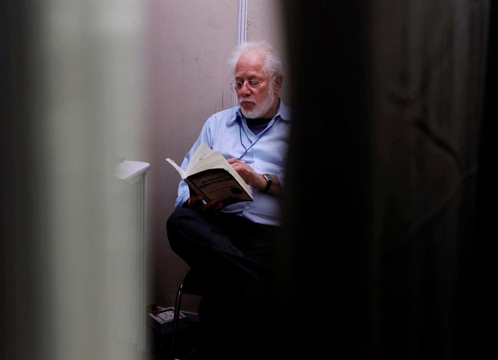 In this 2012 file photo, Michael Ondaatje reads at the back stage green room before presenting his talk at the Jaipur Literature Festival, in Jaipur, in the western Indian state of Rajasthan.