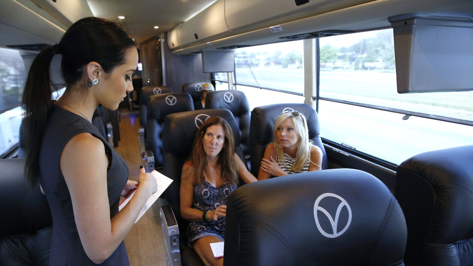 Sarah Moore, left, attendant for Vonlane, explains what Christy Isett, center, and Suzy Galanis can order before their bus departs Dallas en route to Austin on Friday, June 26, 2015. Passengers have the comfort of Wi-Fi and with an onboard attendant and gallery that serves complimentary snacks, meals, and refreshments. It also offers first class seating with ample legroom with complimentary noise canceling headsets. (David Woo/The Dallas Morning News)