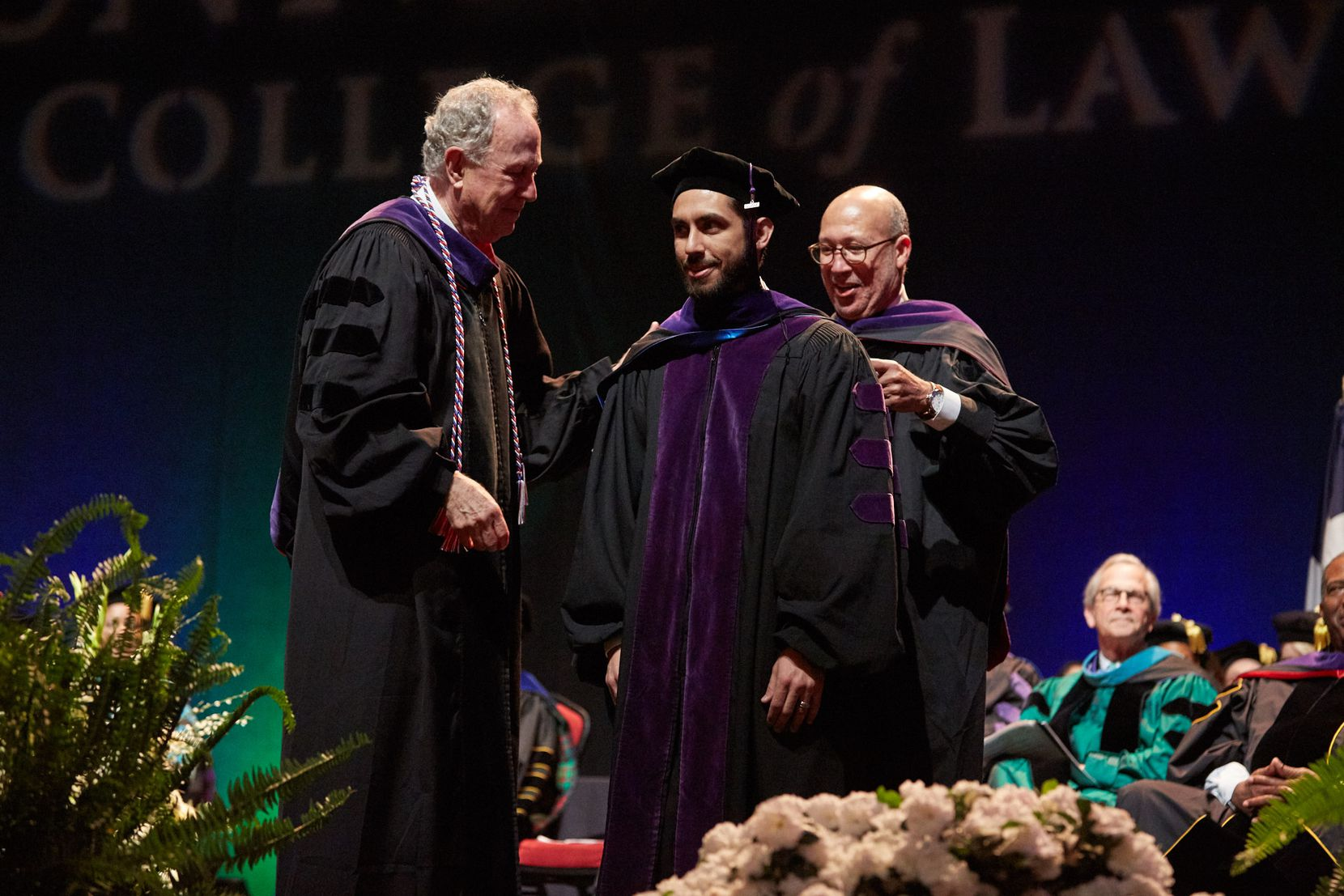 Law student Rafael Valbuena stands on stage during UNT Dallas' first Juris Doctor hooding ceremony on May 20 alongside Dean Royal Furgeson (left) and professor Thomas Perkins.