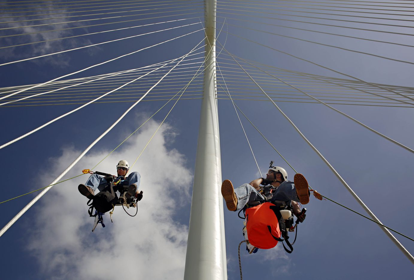 Doug Dickson (left) and Don Cartwright of TranSystems are suspended from ropes as they prepare to inspect the Margaret Hunt Hill Bridge June 12, 2013 in Dallas. The Cleveland, Ohio-based team began work on Monday to inspect the 14-month-old bridge for signs of stress as part of regular maintenance. (G.J. McCarthy/The Dallas Morning News)