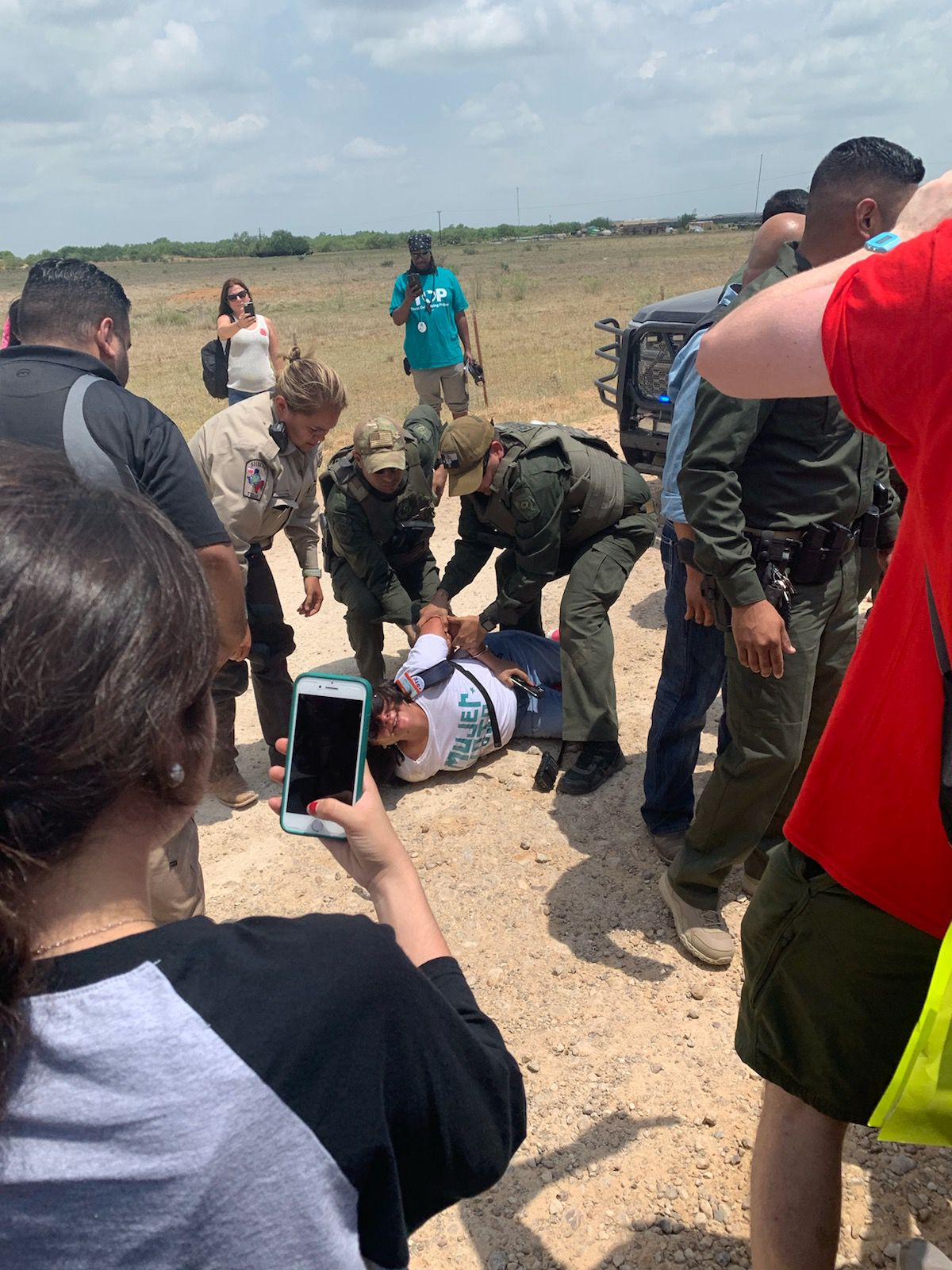 Dimmit County sheriff's deputies arrest a protester at the Carrizo Springs migrant children detention facility.
