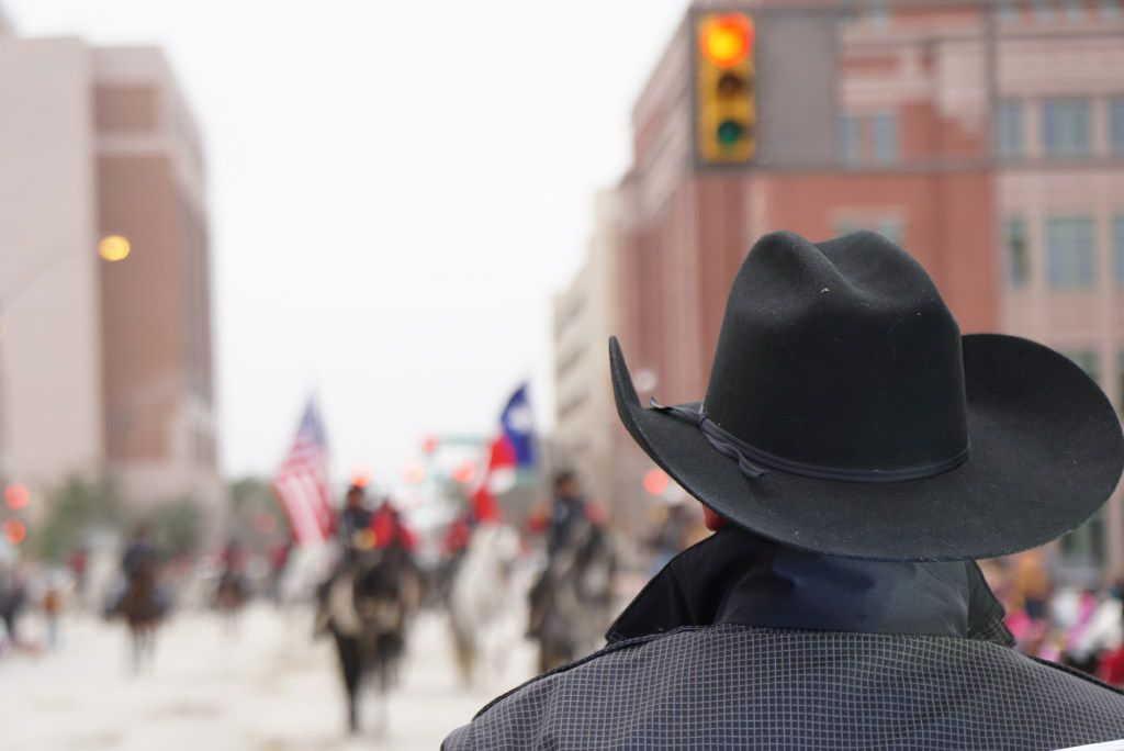 "A Fort Worth police officer looks on during the Fort Worth Stock Show's ""All Western Parade"" earlier this year. Cowboy hats are a normal part of the department's uniforms."
