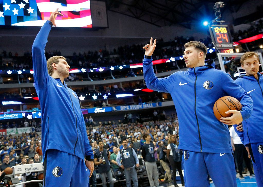 Dallas Mavericks forward Dirk Nowitzki (left) and Dallas Mavericks forward Luka Doncic hgh five following the national anthem before facing the Minnesota Timberwolves at the American Airlines Center in Dallas, Wednesday, April 3, 2019. (Tom Fox/The Dallas Morning News)