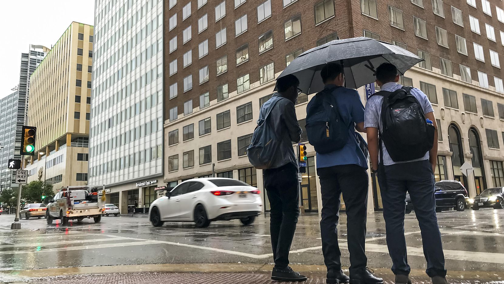 Pedestrians try to take cover from the rain as a thunderstorm rolls through downtown Dallas.