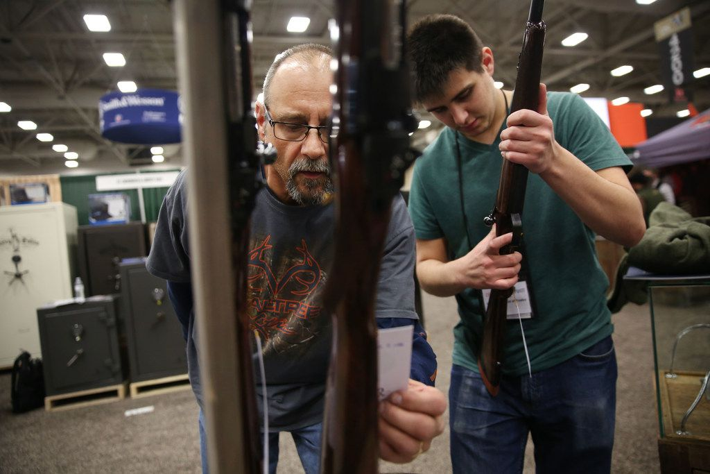 Lenny Perko and his son Lucas Perko look at Rigby firearms during the Dallas Safari Club annual convention and sporting expo at the Kay Bailey Hutchison Convention Center in Dallas on Thursday, Jan. 4, 2018.