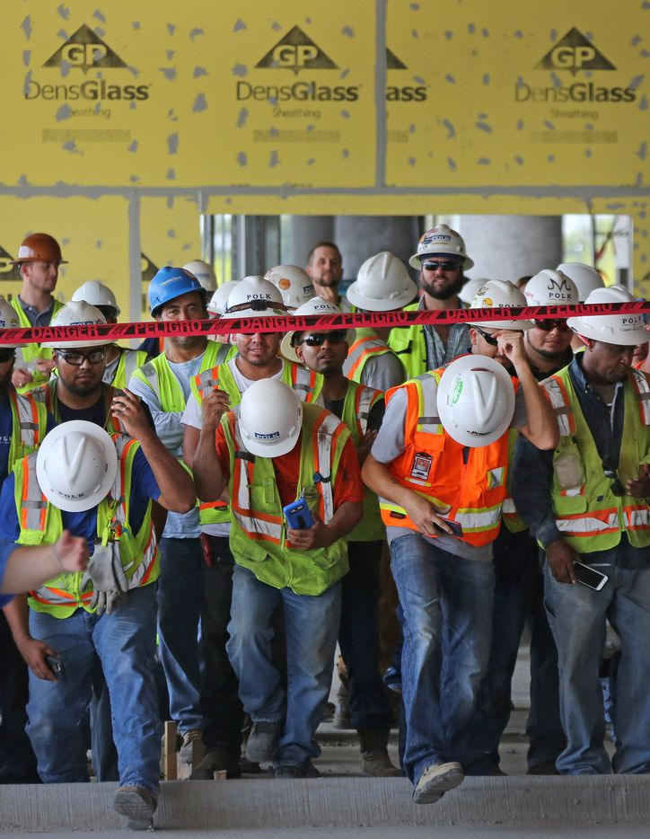 Construction workers gather during a July 18, 2017, ceremony to celebrate the topping off of the Baylor Scott & White Sports Therapy & Research building under construction at The Star in Frisco.  The building is scheduled for a  2018 opening.