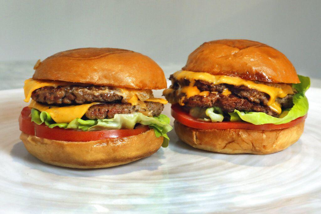 Una hamburguesa Original Impossible Burger, izquierda, y una Cali Burger, de Umami Burger, en esta foto tomada en Nueva York, 3 de mayo de 2019. Ha comenzado una nueva era de alternativas a la carne: Beyond Meat es la primera empresa de carne vegana que vende sus acciones al público e Impossible Burger aparece en menús en todo EEUU. (AP Foto/Richard Drew)