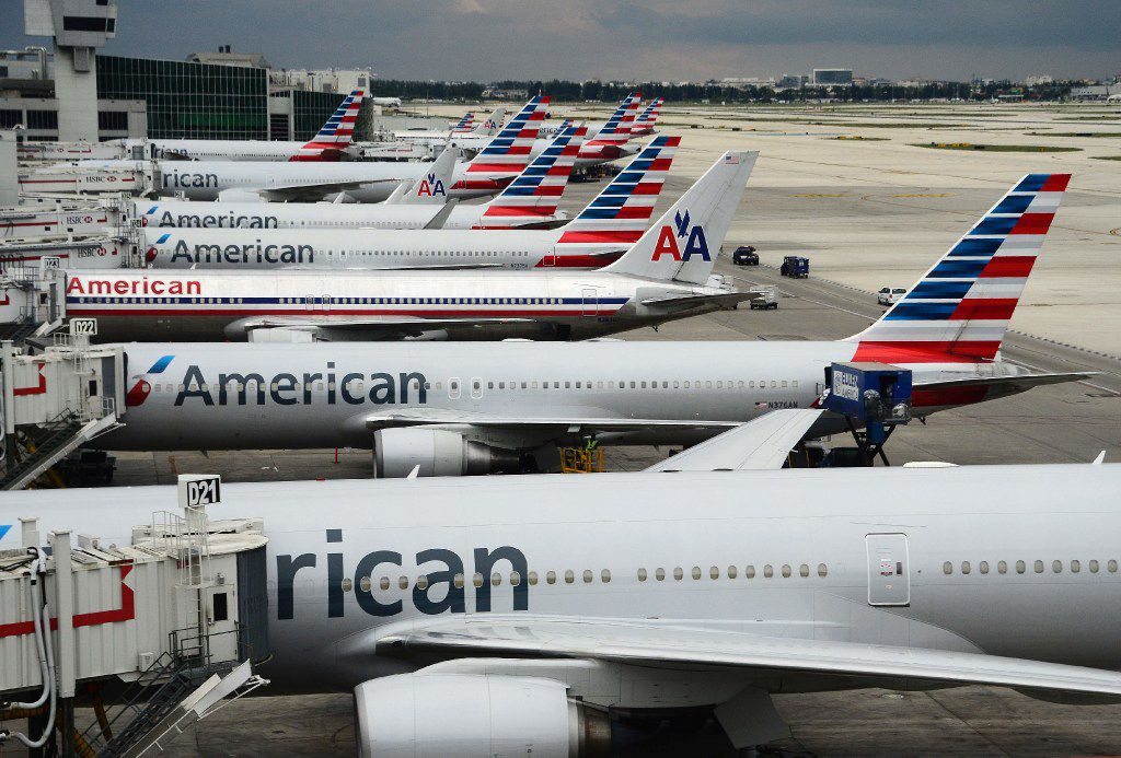 (FILES) This file photo taken on June 8, 2015 shows American Airlines passenger planes  on the tarmac at Miami International Airport in Miami, Florida.   American Airlines said on January 27, 2017 it sees a strong market for ticket sales as it reported lower fourth-quarter earnings but a rise in a closely-watched industry benchmark.Net income in the fourth quarter was $289 million, down from $3.3 billion in the year-ago period. The fourth quarter of 2015 was boosted by $3 billion in tax allowances.  Revenues were $9.8 billion, up 1.7 percent from the year-ago period.  / AFP PHOTO / ROBYN BECKROBYN BECK/AFP/Getty Images
